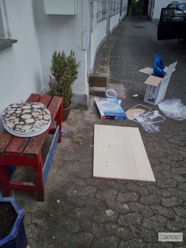 Komposttoilette für den Garten selber bauen_Material liegt wahllos herum, u.a. Brett und Klobrille