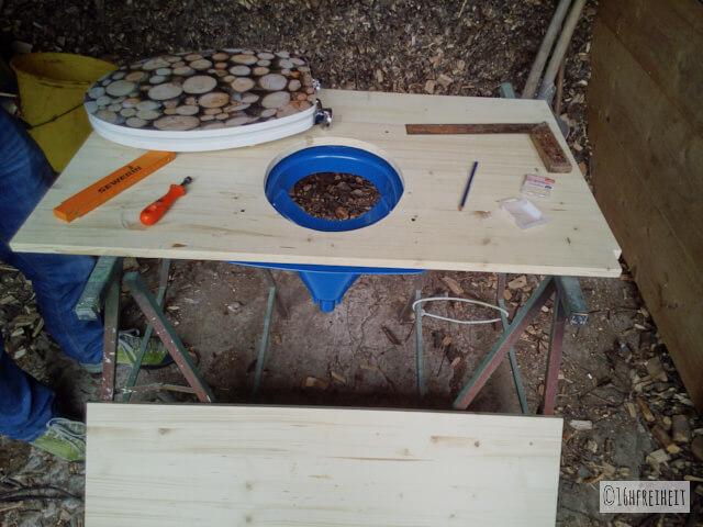 Komposttoilette für den Garten selber bauen_Einbau Separett: Brett mit Loch. Oben auf dem Brett liegt die Klobrille